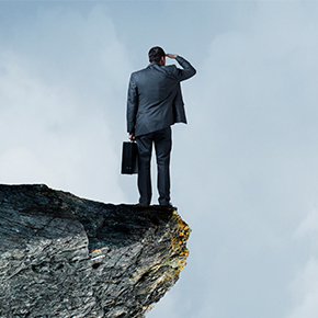 Businessman standing on cliff looking into the distance