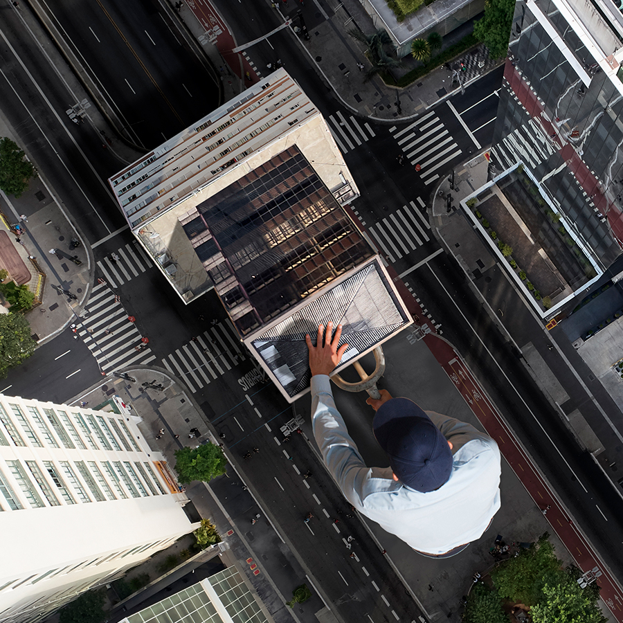 Photo of a man wheeling a building down a street on a dolly